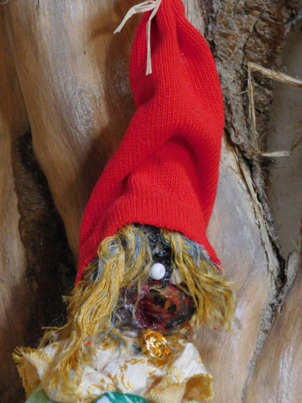 Détail de la tête de la Vertacolutine au bonnet rouge et jupe à fleurs.