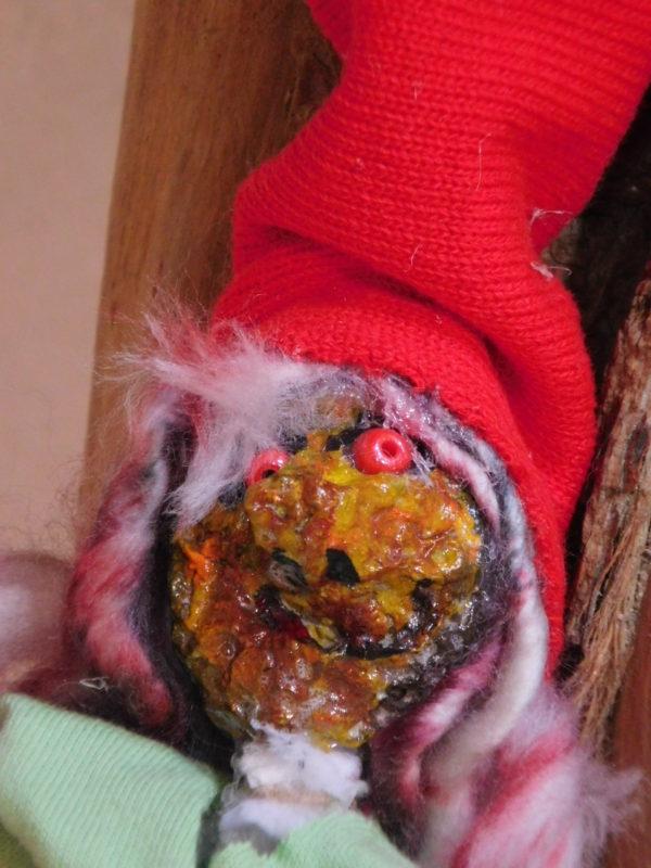 Détail de la tête du Vertacolutin au bonnet rouge et pantalons bouffants.