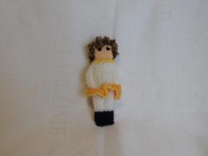 poupée fille tricotée. Elle est vêtue de blanc et porte une jupette orangée. Ses cheveux sont bouclés.