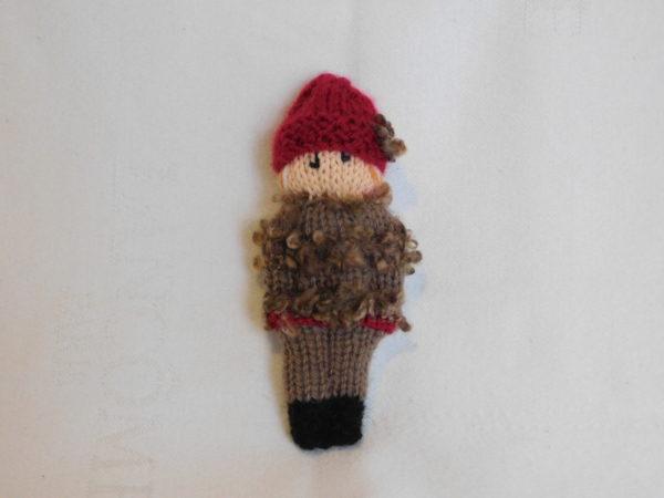 Poupée fille tricotée. Ces vêtements sont marron et rouge et porte un bonnet rouge à fleur marron.