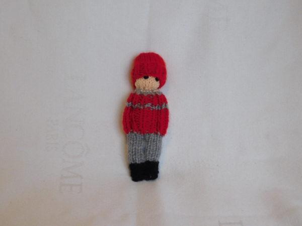 poupée garçon tricotée. Son patalon est gris, son pull est rouge et gris, son bonnet est rouge.