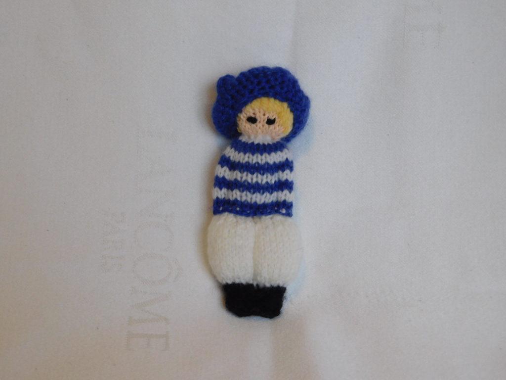 poupée fille tricotée. elle est vêtue d'un pantalon bouffant blanc et d'une marinière blanche et bleue. Elle est coiffée d'un grand béret bleu.