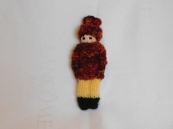 Poupée fille tricotée avec un collant jaune, un pull et un bonnet rouille.